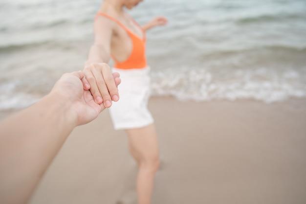 Kobieta, trzymając rękę chłopaka razem działa na plaży.