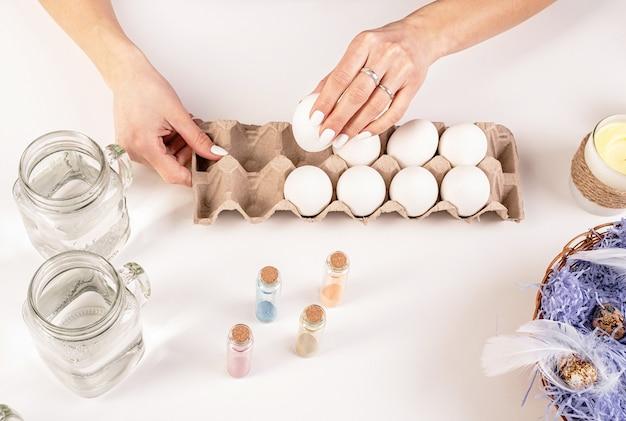 Kobieta trzymając się za ręce białe jajko gotowe do pisanki kolorowanki widok z góry