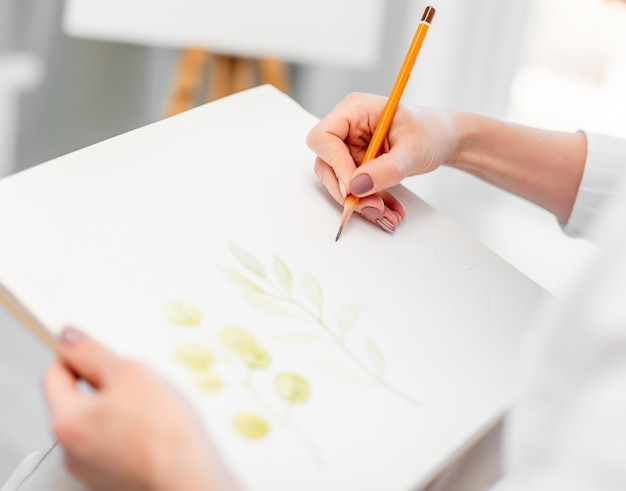 Kobieta trzymając się za ręce biały papier na płótnie i ołówek graficzny i rysunek szkic