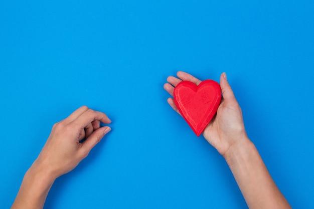 Kobieta trzymając się za ręce czerwone drewniane serce