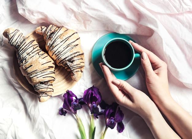 Kobieta trzymając się za ręce filiżankę kawy w łóżku. piękne kwiaty i zegarek z bransoletką