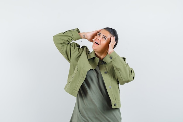 Kobieta trzymając się za ręce na głowie w kurtce, t-shirt i patrząc zdziwiony