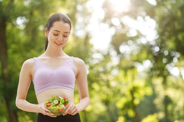 Kobieta trzymając się za ręce sałatki świeże lato z surowych warzyw ogórki pomidory sałata w misce.