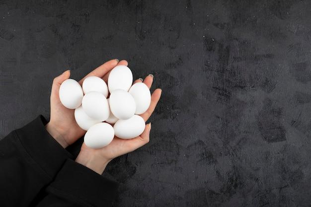 Kobieta trzymając się za ręce stos surowych jaj na czarnym tle.