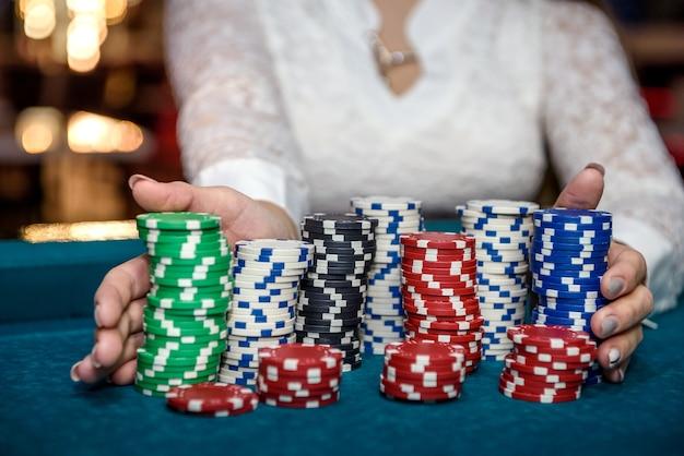 Kobieta trzymając się za ręce stosy żetonów w kasynie na stole