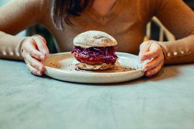 Kobieta trzymając się za ręce talerz wegetariańskiego burgera z burakami
