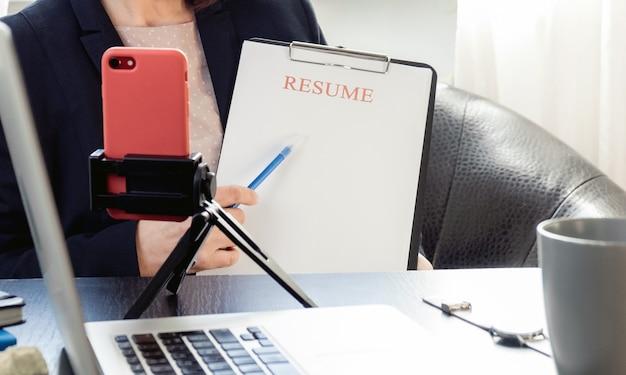 Kobieta trzymając się za ręce wznowić aplikację w pobliżu jej pracy z laptopem.