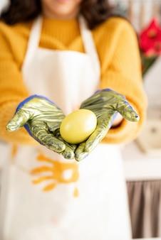 Kobieta trzymając się za ręce żółte kolorowe pisanki