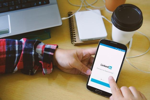 Kobieta trzymając smartfon pod ręką i zacząć korzystać z aplikacji linkedin