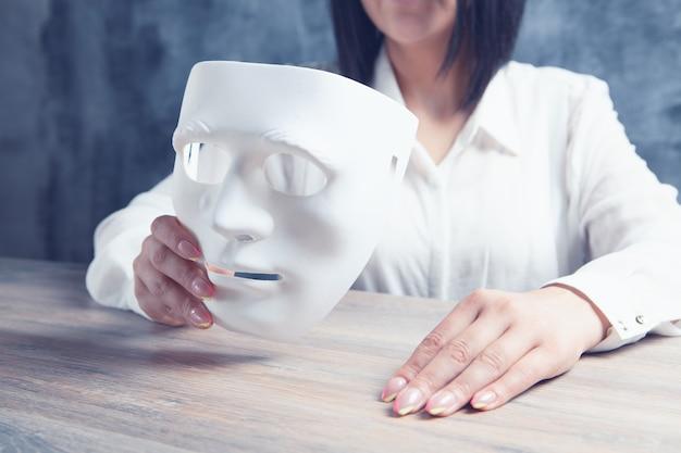 Kobieta trzymająca anonimową maskę przy stole