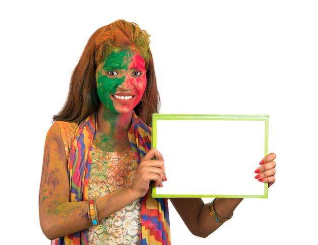 Kobieta trzymająca biały szyld z twarzą pomalowaną na kolor w festival of colour holi. na białym tle portret