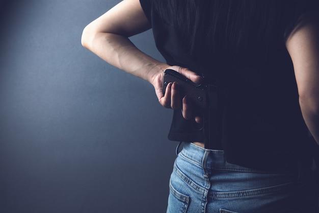 Kobieta trzymająca broń za plecami
