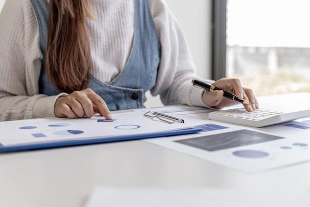Kobieta trzymająca długopis wskazujący na dokument na biurku i naciskająca kalkulator, sprawdza numery na dokumentach finansowych przygotowanych przez dział finansowy. pojęcie audytu finansowego.
