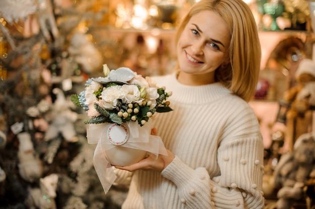 Kobieta trzymająca doniczkę z białymi kwiatami ozdobiona zielonymi liśćmi i gałęziami jodły