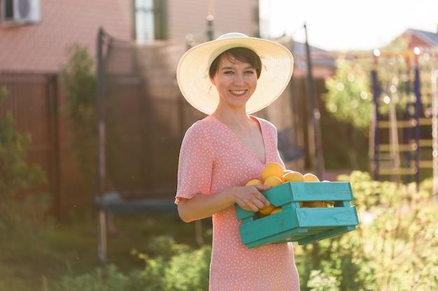 Kobieta trzymająca drewnianą skrzynię ze świeżymi organicznymi cytrynami z jesiennych zbiorów rolniczych i rolnictwa