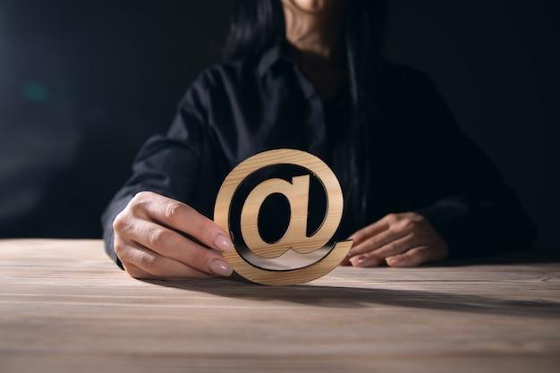 Kobieta trzymająca drewniany znak e-mail na tle stołu