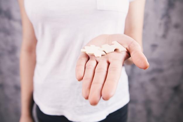 Kobieta trzymająca dwa kawałki układanki