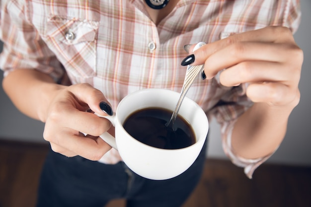 Kobieta trzymająca filiżankę kawy z łyżką