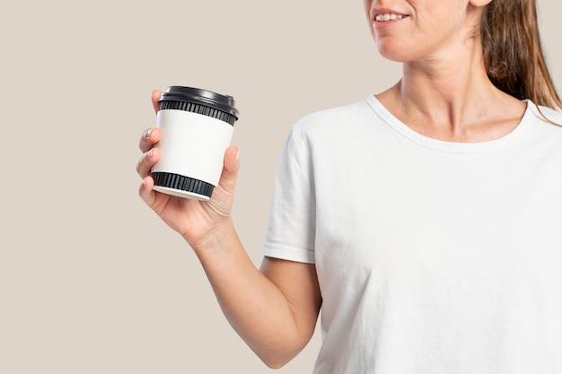 Kobieta trzymająca filiżankę kawy z miejscem na projekt rękawa