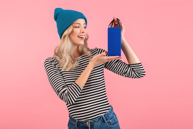 Kobieta trzymająca głośnik bezprzewodowy słuchająca muzyki ubrana w pasiastą koszulę i niebieski kapelusz uśmiechnięty szczęśliwy pozytywny nastrój pozujący na różowo