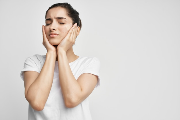 Kobieta trzymająca głowę uraz problemy zdrowotne jasne tło