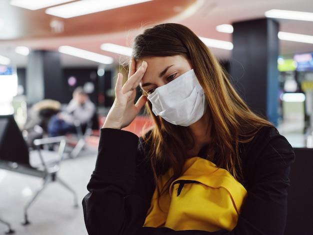 Kobieta trzymająca głowę w masce medycznej oczekujący pasażer lotniska