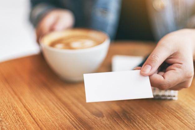 Kobieta trzymająca i dająca komuś pustą pustą wizytówkę podczas picia kawy
