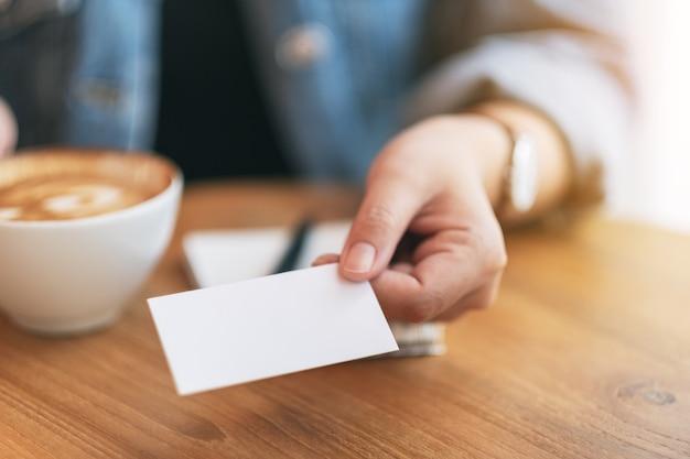Kobieta trzymająca i dająca komuś pustą pustą wizytówkę podczas picia kawykobieta trzymająca i dająca komuś pustą pustą wizytówkę podczas picia kawy