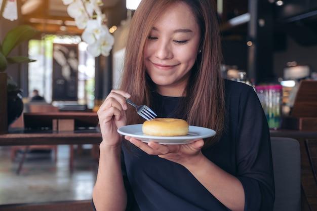 Kobieta trzymająca i jedząca kawałek pączka