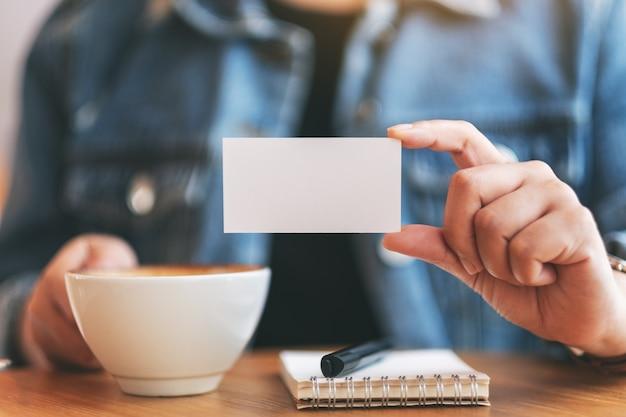 Kobieta trzymająca i pokazująca komuś pustą wizytówkę podczas picia kawy