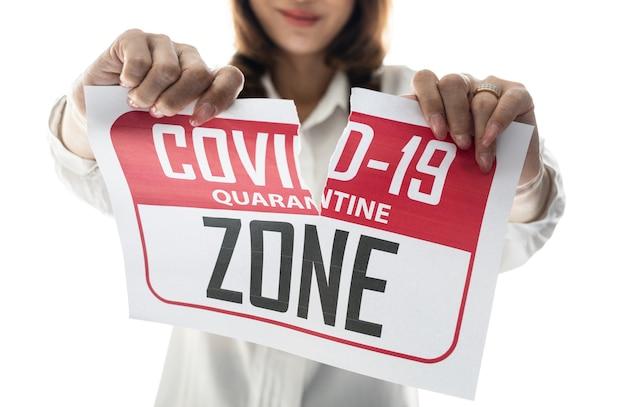 Kobieta trzymająca i rozdzierająca papier ze strefą kwarantanny covid-19. pomysł lub koncepcja szczęścia, wolności i dobrego samopoczucia po zakończeniu i odzyskaniu z coronarivus.