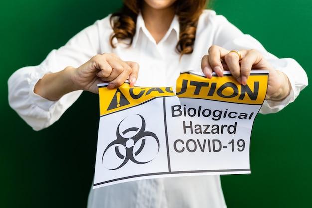 Kobieta trzymająca i rozrywająca papier z ostrzeżeniem covid-19 przed słowami o zagrożeniach biologicznych. pomysł lub koncepcja szczęścia, wolności i dobrego samopoczucia po zakończeniu i odzyskaniu z coronarivus.