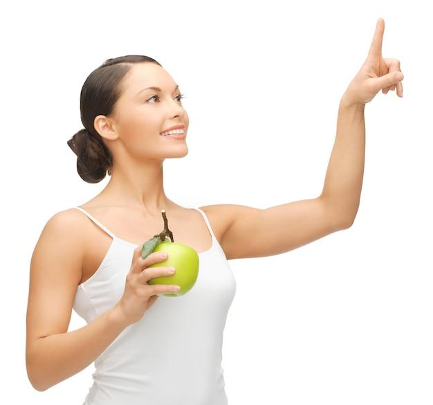 Kobieta trzymająca jabłko i pracująca z czymś wyimaginowanym