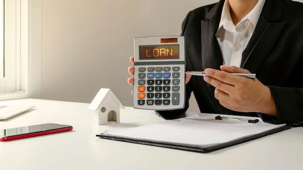 Kobieta trzymająca kalkulator i wskazująca długopisem tekst pożyczki na kalkulatorze koncepcji pożyczki dla mśp