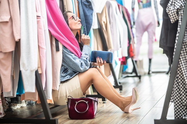 Kobieta trzymająca kartę debetową lub kredytową marzy o swoich możliwościach zakupowych siedzących wśród wieszaków na ubrania w centrum handlowym.