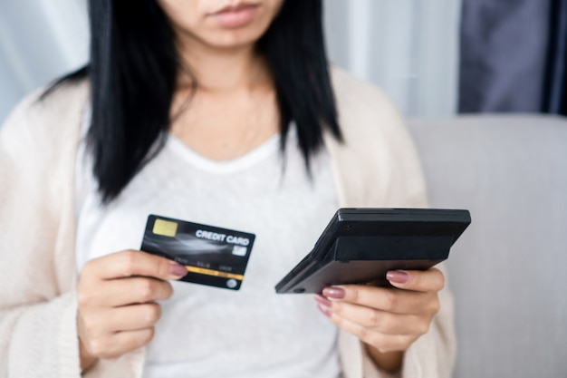 Kobieta trzymająca kartę kredytową i kalkulator przekraczająca zaległą płatność