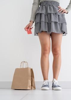 Kobieta trzymająca kartę kredytową, w pobliżu ekologiczne papierowe torby na zakupy