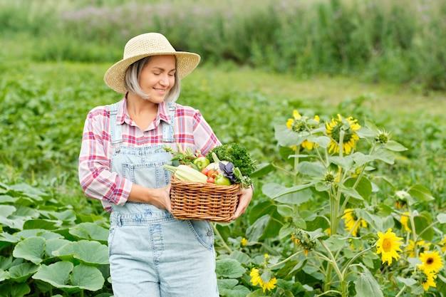Kobieta trzymająca kosz pełen organicznych warzyw i korzeni zbiorów na ekologicznej farmie bio. jesienne zbiory warzyw.