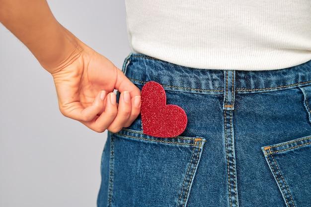 Kobieta trzymająca małe błyszczące czerwone serce wkłada je lub zdejmuje kieszeń dżinsów. dzielenie się i otrzymywanie walentynek, miłość do ciebie