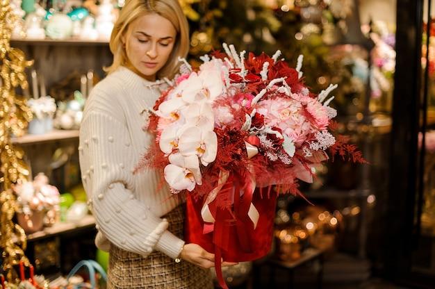 Kobieta trzymająca ogromne pudełko ozdobione taśmą w różowe orchidee i hydrandy z czerwonym zdobieniem