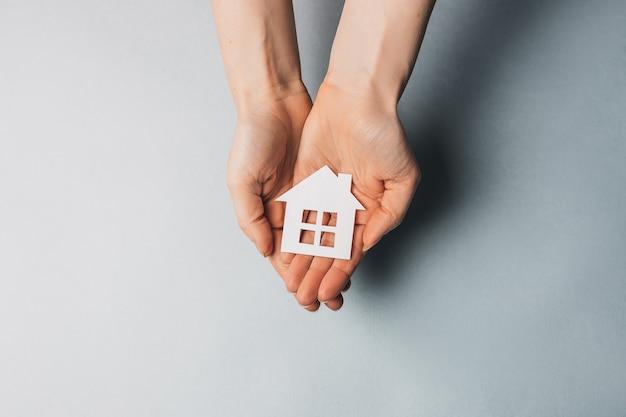 Kobieta trzymająca papierowy dom w dłoniach ze słońcem na jasnoniebieskiej powierzchni