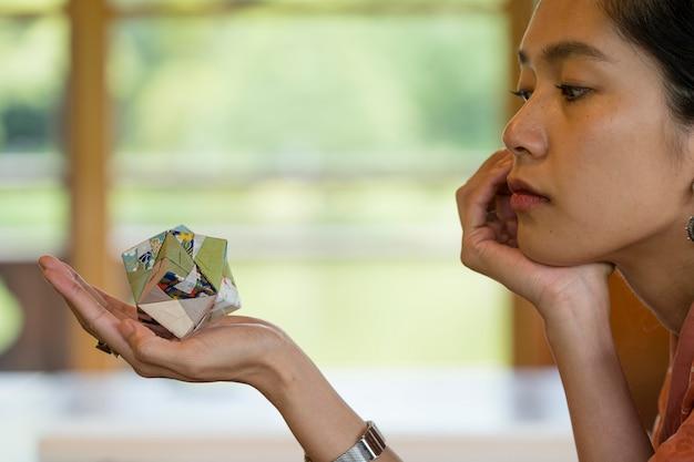 Kobieta trzymająca przedmiot origami