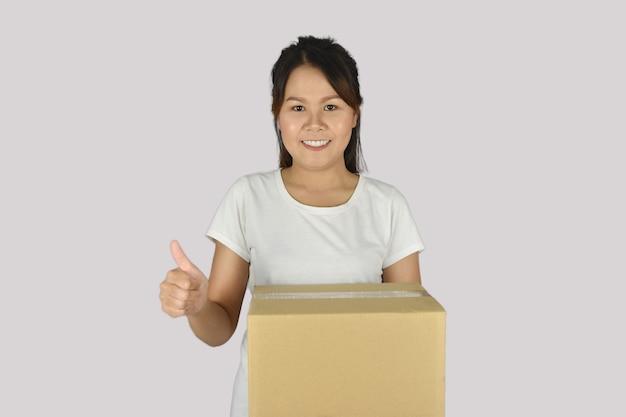 Kobieta trzymająca pudła w rękach i pokazująca kciuki w górę na szarej przestrzeni