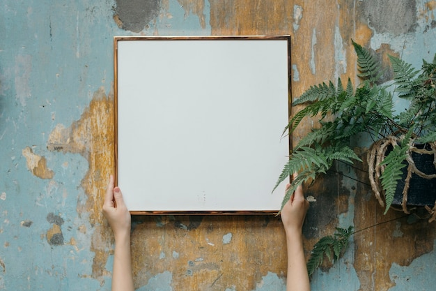 Kobieta trzymająca pustą ramkę przy ścianie grungy