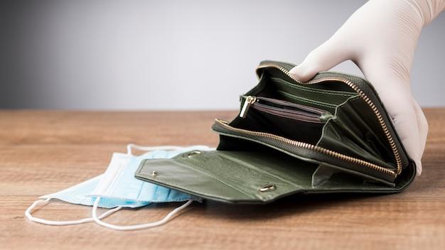 Kobieta trzymająca pusty portfel obok maski na twarz
