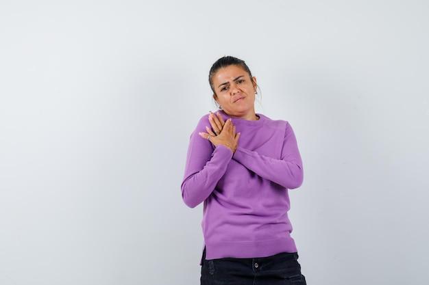 Kobieta trzymająca ręce na klatce piersiowej w wełnianej bluzce i wyglądająca ponuro