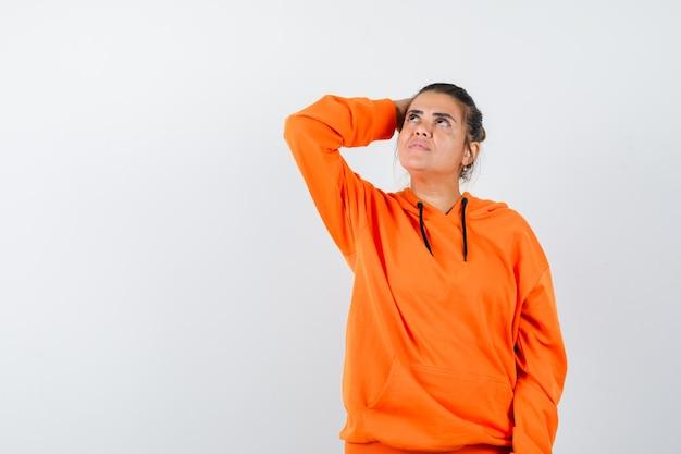 Kobieta trzymająca rękę na głowie w pomarańczowej bluzie z kapturem i wyglądająca na marzycielską