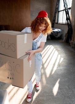 Kobieta trzymająca rzeczy w kartonach do przeprowadzki w nowym domu