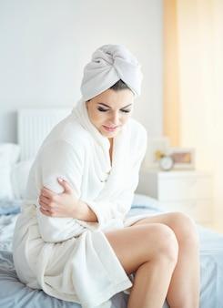 Kobieta trzymająca się za brzuch w sypialni