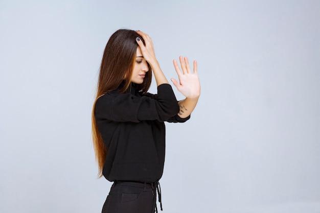 Kobieta trzymająca się za czoło, bo boli ją głowa.